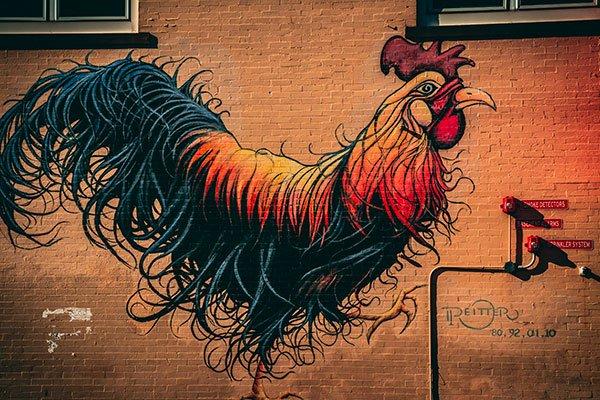 Graffiti d'un coq sur un mur.